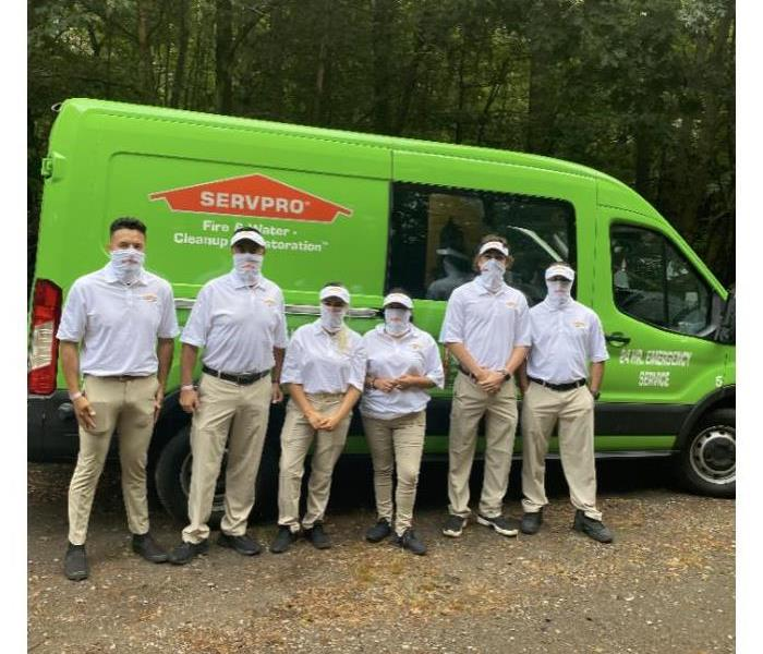a team in front of a green SERVPRO van